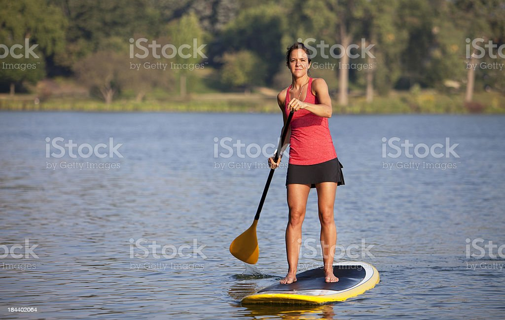 Athletic Woman Paddle Boarding on a Calm Midwestern Lake. stock photo
