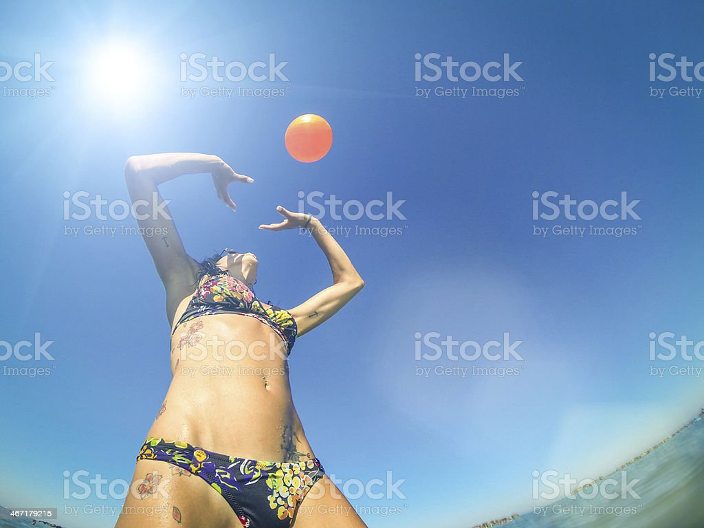 Athletic woman playing beach volley in the sea royalty-free stock photo
