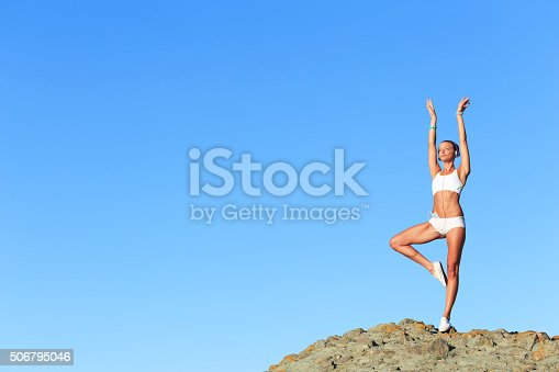816941230istockphoto Athletic woman practicing on top of rock 506795046