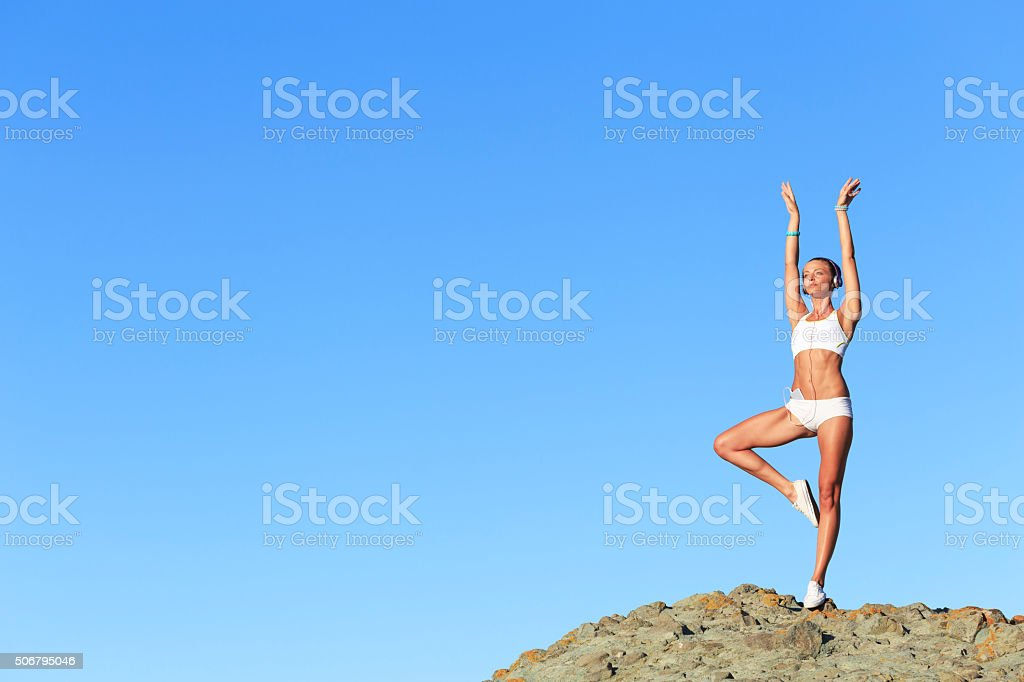 Athletic woman practicing on top of rock stock photo