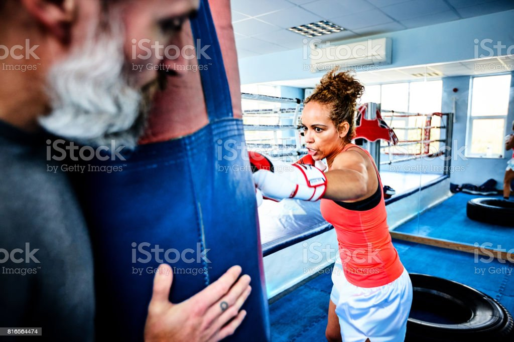 Athletic woman punching a bag in gym stock photo