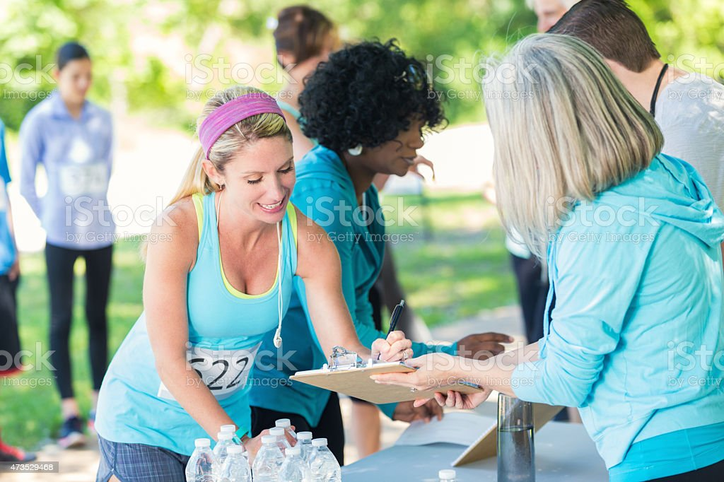Athletic woman registering for marathon race at sunny park stock photo