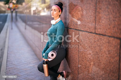 1091470492 istock photo Athletic woman resting while leaning on a marble building wall in a downtown area 1091469252