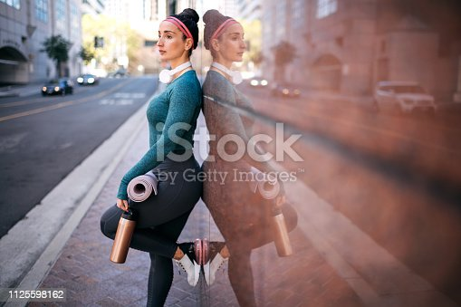 1091470492 istock photo Athletic woman resting while leaning on a marble building wall in a downtown area 1125598162