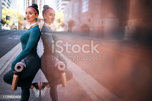 1091470492 istock photo Athletic woman resting while leaning on a marble building wall in a downtown area 1125600404