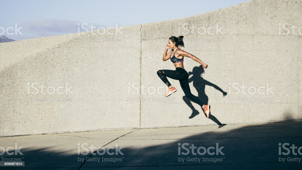 Athletic woman running and jumping outdoors stock photo
