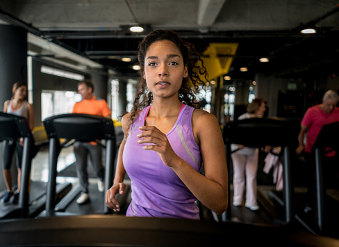 Portrait of an athletic woman running at the gym on the treadmill - fitness concepts