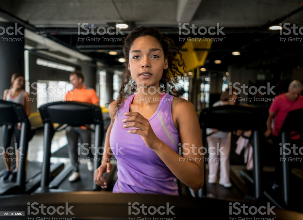 Athletic woman running at the gym stock photo