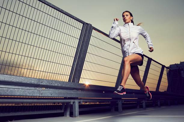 athletische frau läuft während sonnenuntergang auf dem dach von parkplatz, garage - joggerin stock-fotos und bilder