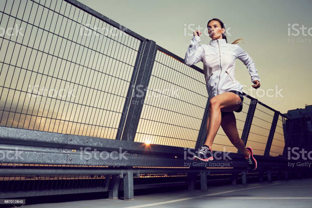 Athletic woman running during sunset on rooftop of parking, garage stock photo