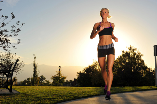 Athletic Woman Running In The Park Stock Photo - Download Image Now