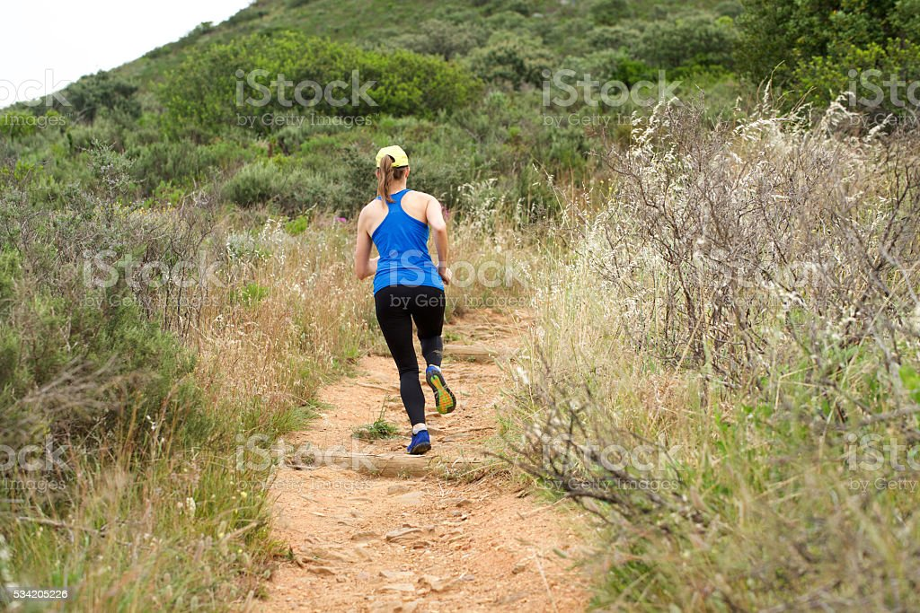Athletic woman running on dirt trail outside stock photo