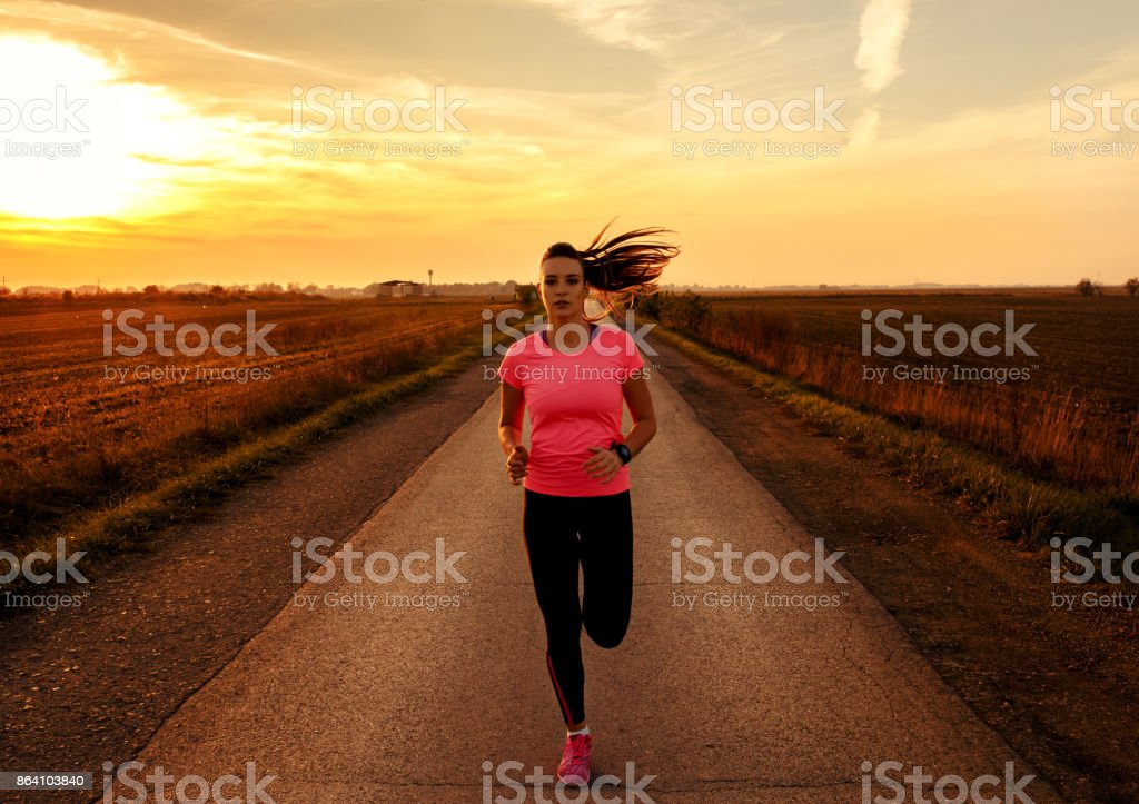 Athletic woman running on rural road during sunset. royalty-free stock photo