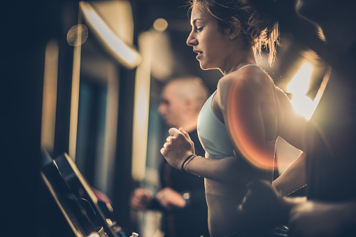 Determined female athlete jogging on treadmill in a gym while other people are beside her.