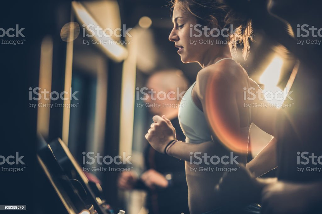 Athletic woman running on treadmills during sports training in a health club. stock photo