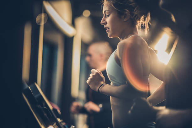 athletic woman running on treadmills during sports training in a health club. - health club stock photos and pictures
