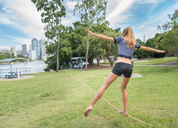 sportliche frau slacklinen, brisbane, australien - slackline stock-fotos und bilder