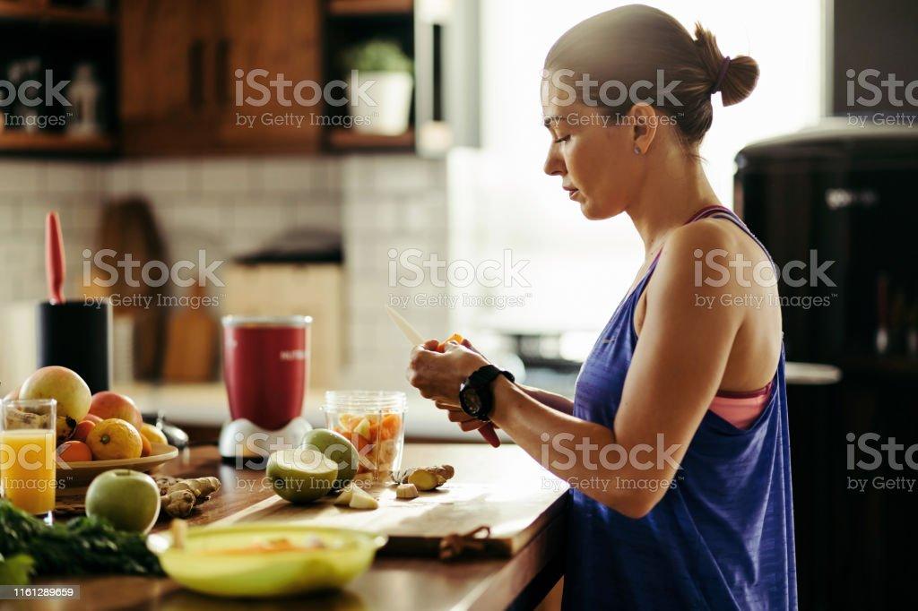 부엌에서 스무디를 준비하는 동안 과일을 슬라이스 운동 여자. - 로열티 프리 건강한 생활방식 스톡 사진