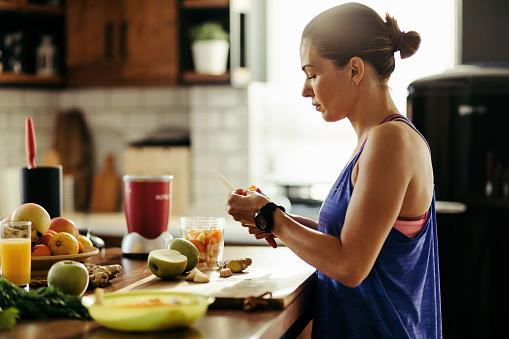 부엌에서 스무디를 준비하는 동안 과일을 슬라이스 운동 여자 건강한 생활방식에 대한 스톡 사진 및 기타 이미지