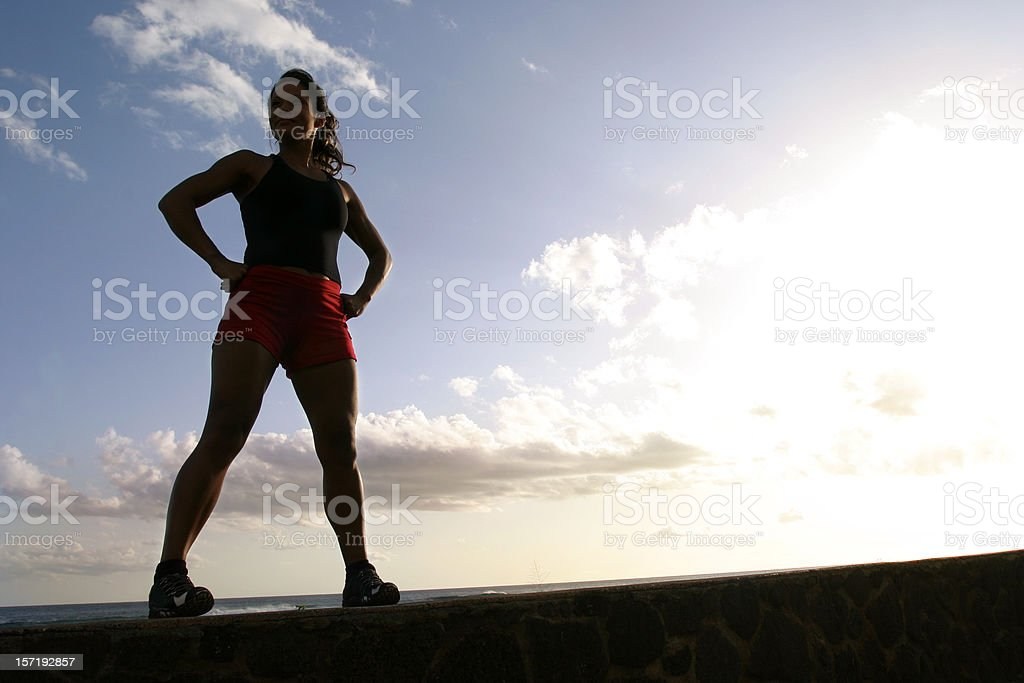 Athletic Woman Stands Victorious with Hands on Hips royalty-free stock photo