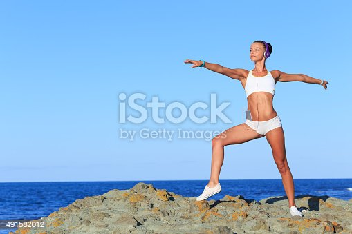 816941230istockphoto Athletic Woman Stretching at the Beach 491582012