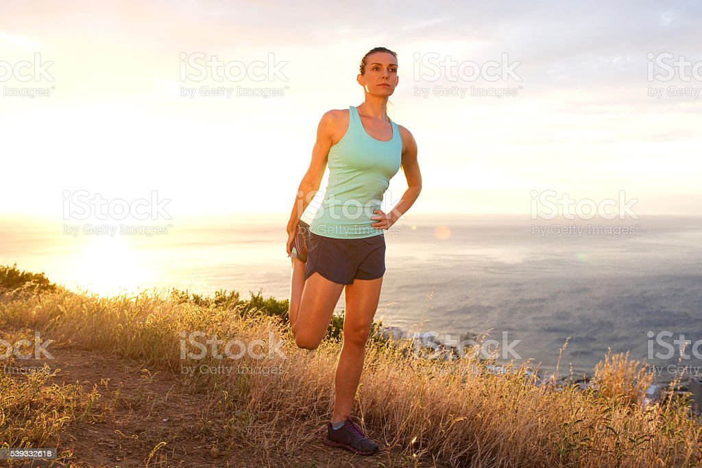 Athletic woman stretching outdoors by sunset stock photo