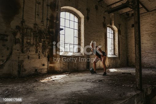istock Athletic woman swinging kettlebell  in an old building 1059617568