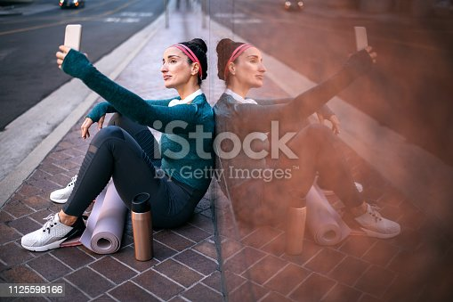 1091470492 istock photo Athletic woman taking a selfie with her smart phone while resting and sitting with her back against a marble building wall in a city street 1125598166