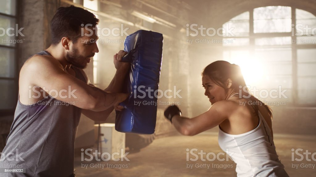 Athletic Woman Trains Her Punches On A Punching Bag That Her