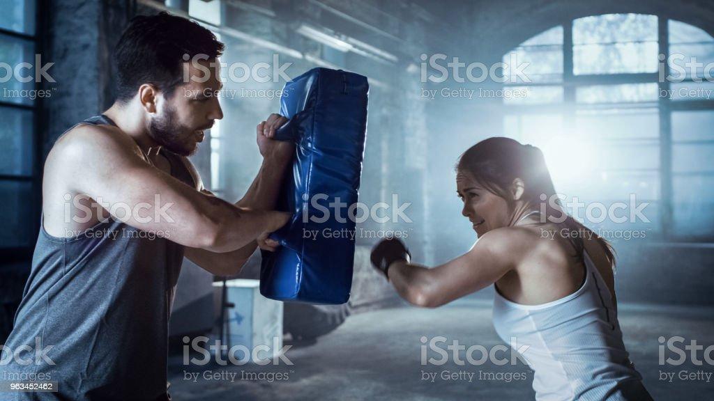 Athletic Woman trenuje jej ciosy na punching bag, że jej partner / trener posiada. Ona jest profesjonalnym wojownikiem i pracuje w Hardcore Gym. - Zbiór zdjęć royalty-free (Boks - sport)