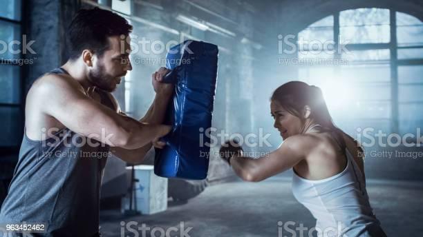 Athletic Woman Trenuje Jej Ciosy Na Punching Bag Że Jej Partner Trener Posiada Ona Jest Profesjonalnym Wojownikiem I Pracuje W Hardcore Gym - zdjęcia stockowe i więcej obrazów Boks - sport