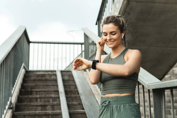 Athletic woman using smartwatch during her fitness workout on city street stock photo