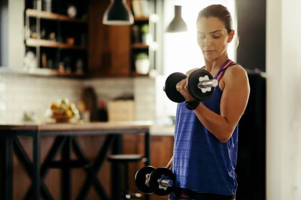 mujer atlética de levantamiento de pesas mientras hace ejercicio en casa. - culturismo fotografías e imágenes de stock