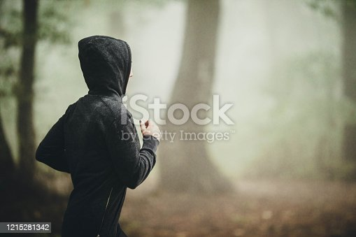 Young female athlete with a hood running in autumn day at misty nature. Copy space.