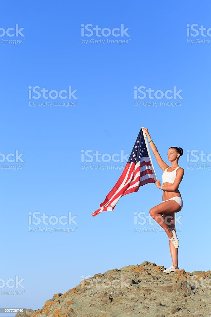 Athletic Woman with american flag on top of rock stock photo