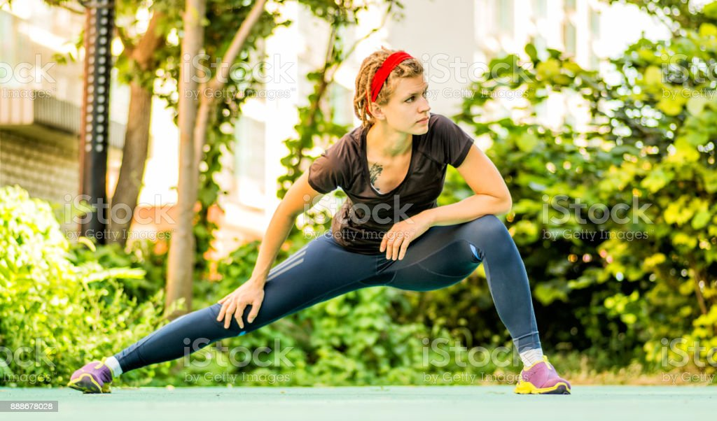 athletic woman with dreadlocks is making workout in a park stock photo