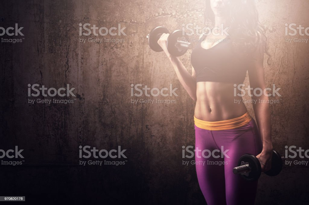 Athletic woman with dumbbells training in gym stock photo
