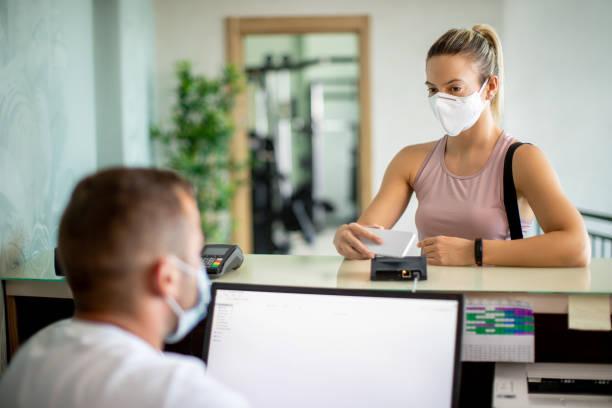 mulher atlética com máscara facial usando telefone inteligente enquanto verificava na academia. - comodidades para lazer - fotografias e filmes do acervo