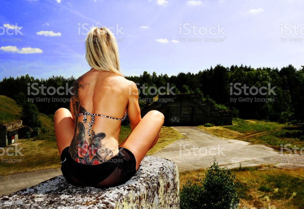 Athletic woman with tattos posing in the nature stock photo