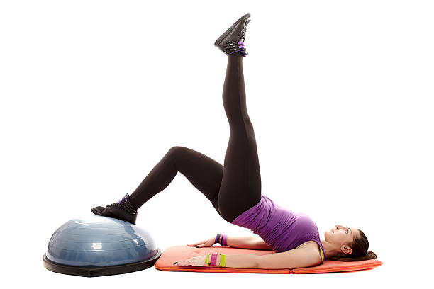 Athletic woman working her legs and bottom on bosu ball stock photo