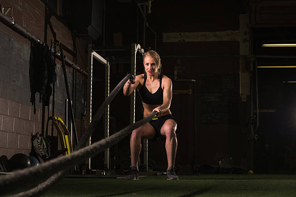 Athletic woman working out with a rope at gym stock photo