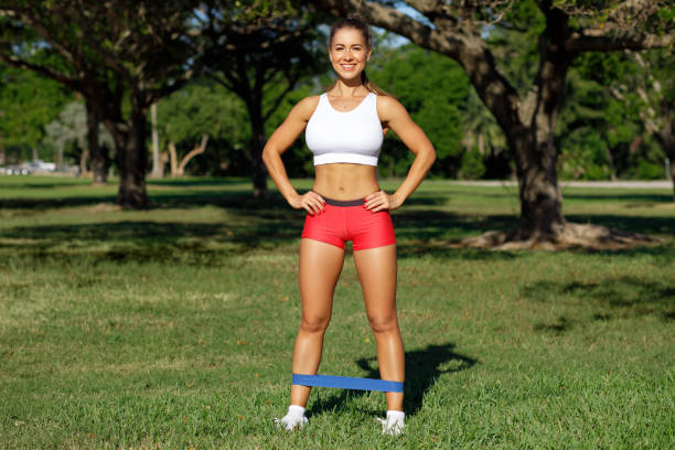 Athletic woman workout with resistance band outdoors. Fitness girl doing exercise for leg at the park stock photo