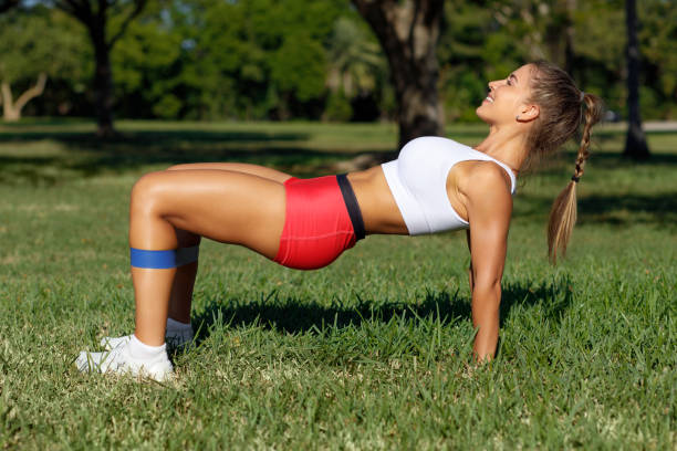 Athletic woman workout with resistance band outdoors. Fitness girl doing exercise for glutes at the park stock photo