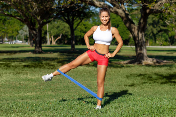 Athletic woman workout with resistance band outdoors. Fitness girl doing exercise for legs at the park stock photo