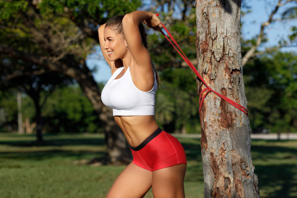 Athletic woman workout with resistance band outdoors. Fitness girl doing exercise for triceps at the park stock photo