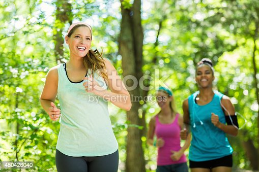 1051098428 istock photo Athletic women running together on trail in sunny park 480426040