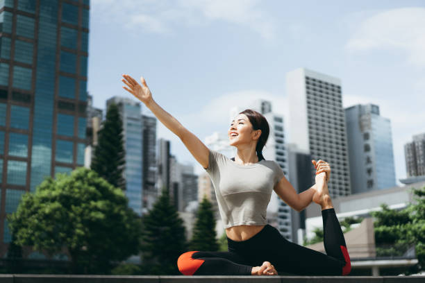 Athletic young Asian woman practicing yoga outdoors in city park against urban cityscape in the morning