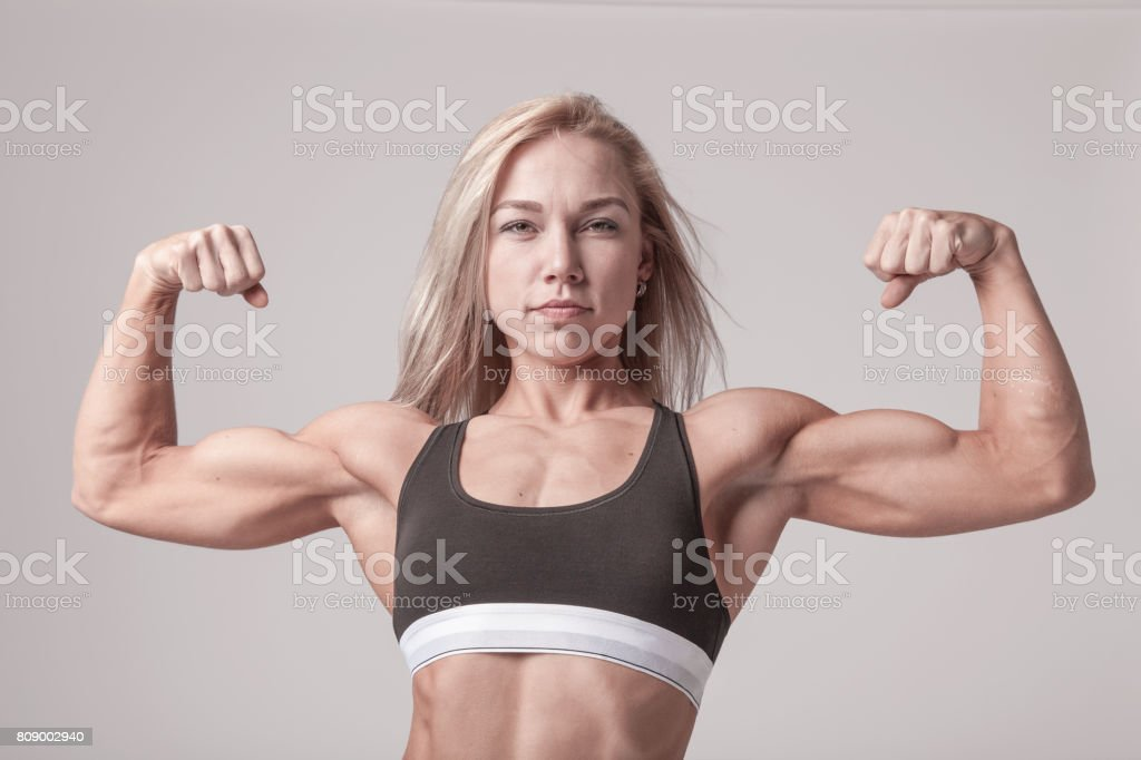 Athletic young blonde woman showing bicep muscles on the soft light background stock photo
