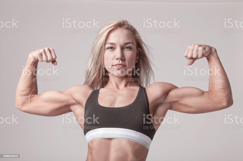 Athlétique jeune femme blonde montrant biceps muscles sur le doux fond clair - Photo