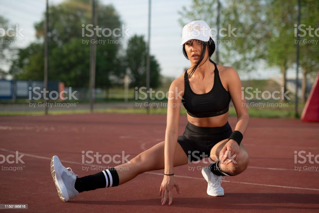 Athletic young Caucasian woman stretching legs on sports court ,...
